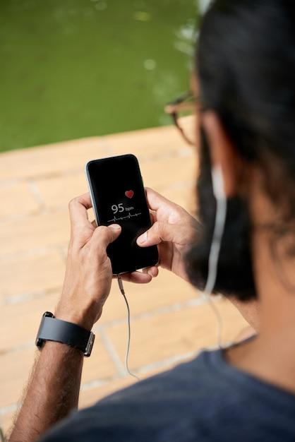 Homem corredor, tendo o pulso com um aplicativo móvel Foto gratuita