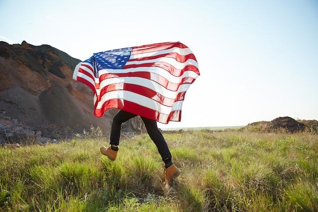 Homem correndo com eua banner na natureza Foto gratuita