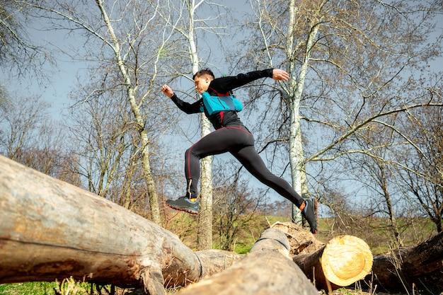 Homem correndo em um parque ou floresta contra o espaço das árvores Foto gratuita