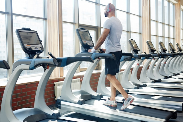 Homem correndo na esteira no ginásio moderno Foto gratuita