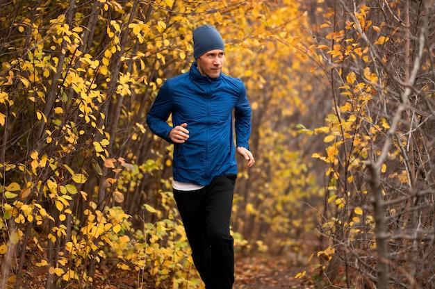 Homem correndo na trilha na floresta Foto gratuita