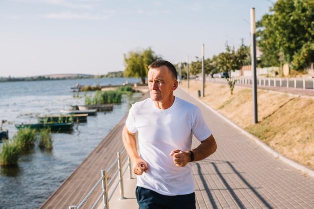 Homem correndo pelo lago tiro médio Foto gratuita