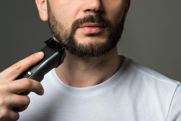 Homem corta a barba Foto Premium