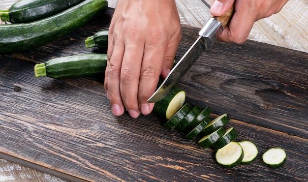 Homem cortando abobrinhas frescas em fatias sobre uma tábua sobre uma mesa de madeira Foto gratuita