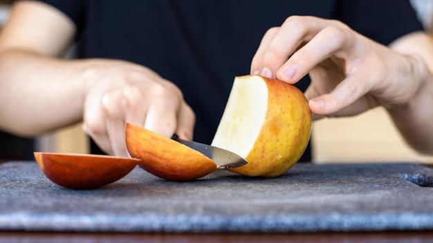 Homem cortando maçã em uma placa de cozinha usando uma faca Foto gratuita