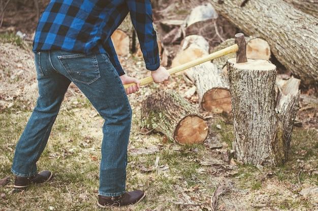 Homem cortando madeira com um machado durante o dia Foto gratuita