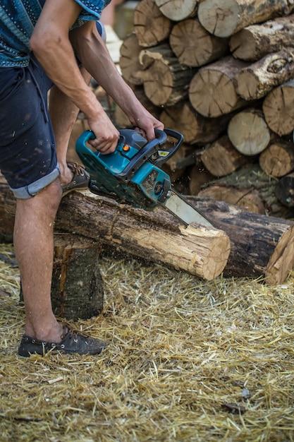 Homem cortando madeira com uma serra elétrica Foto gratuita