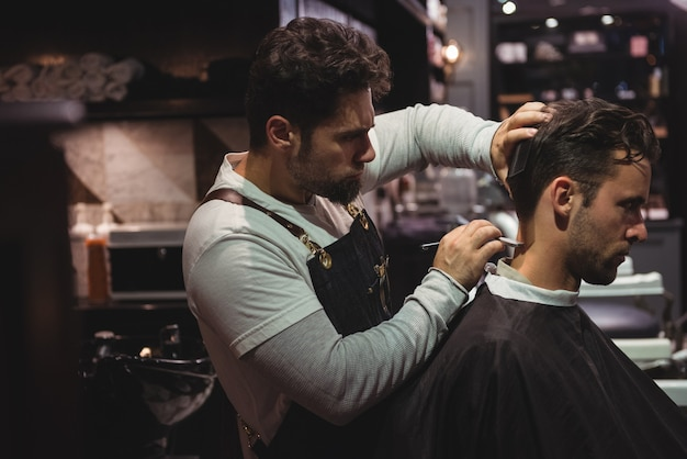 Homem cortando o cabelo com navalha Foto gratuita