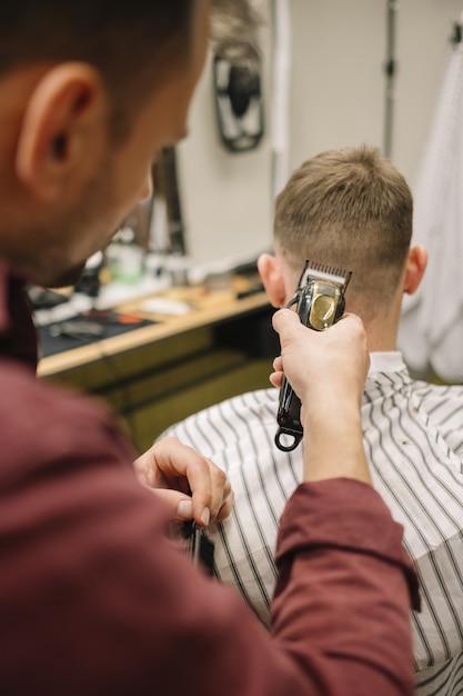 Homem cortando o cabelo em uma barbearia Foto gratuita