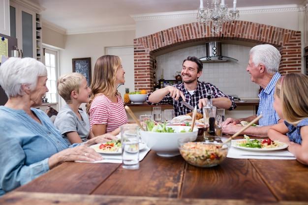 Homem cortando peru assado ao fazer uma refeição com sua família Foto Premium