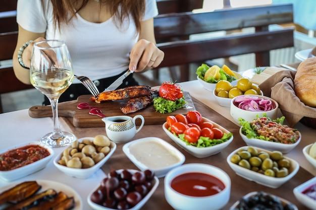 Homem, corte, truta grelhada, azeitonas, tomate, mangal, salada, berinjelas, vista lateral Foto gratuita