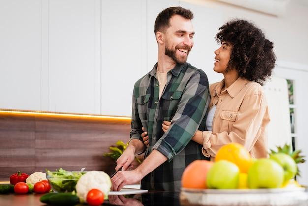 Homem cozinhando e olhando para a namorada Foto gratuita
