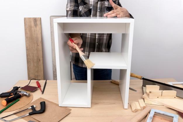 Homem criando um armário da vista frontal de madeira Foto gratuita