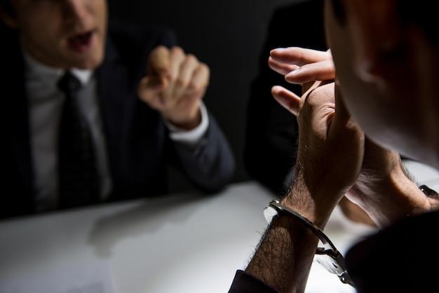 Homem criminoso com algemas sendo entrevistado na sala de interrogatório Foto Premium