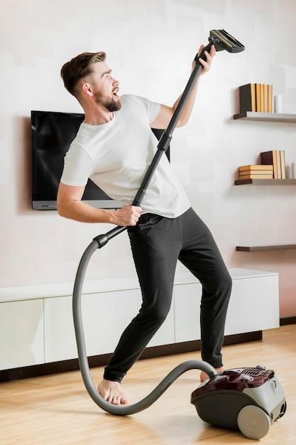 Homem dançando com aspirador Foto gratuita