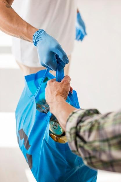 Homem dando a um voluntário uma sacola com doações Foto gratuita