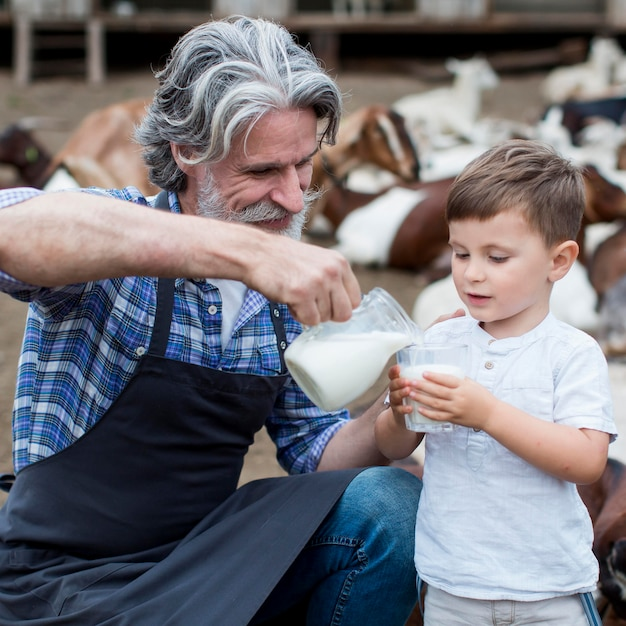 Homem dando leite de cabra ao menino Foto gratuita