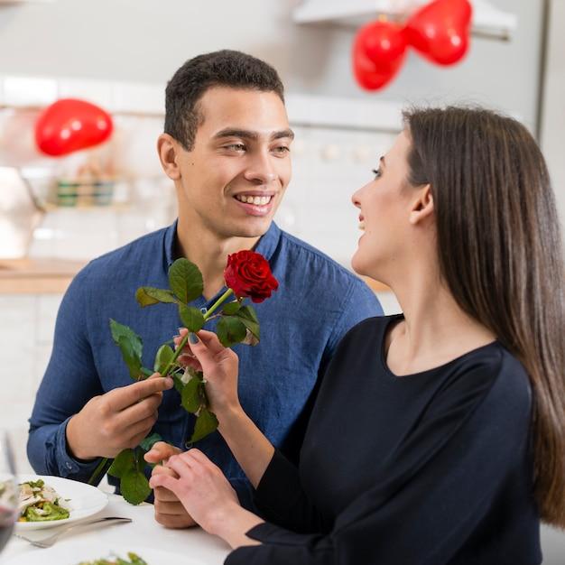 Homem dando uma rosa para sua linda namorada no dia dos namorados Foto gratuita