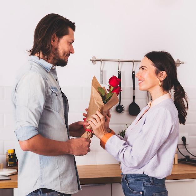 Homem, dar, rosas vermelhas, buquê, para, mulher, em, cozinha Foto gratuita