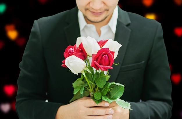 Homem, dar, vermelho branco, buquê, rosas, para, alguém, em, valentine's day Foto gratuita