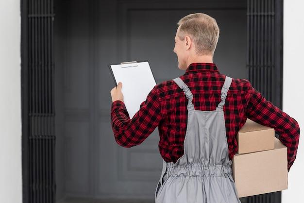Homem de alto ângulo, entregando o pacote Foto gratuita