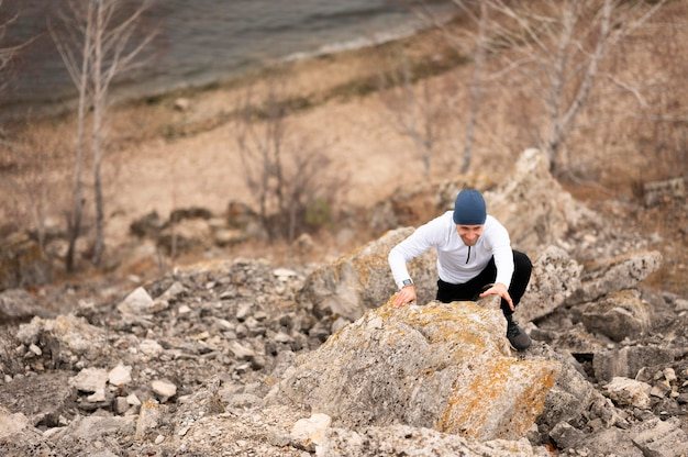 Homem de alto ângulo escalando rochas Foto Premium