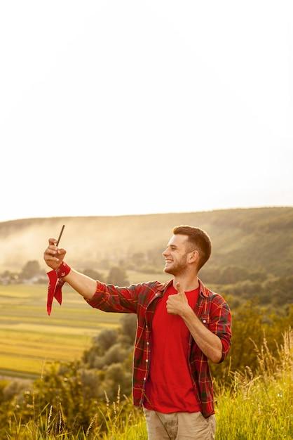 Homem de alto ângulo na montanha tomando selfie Foto gratuita