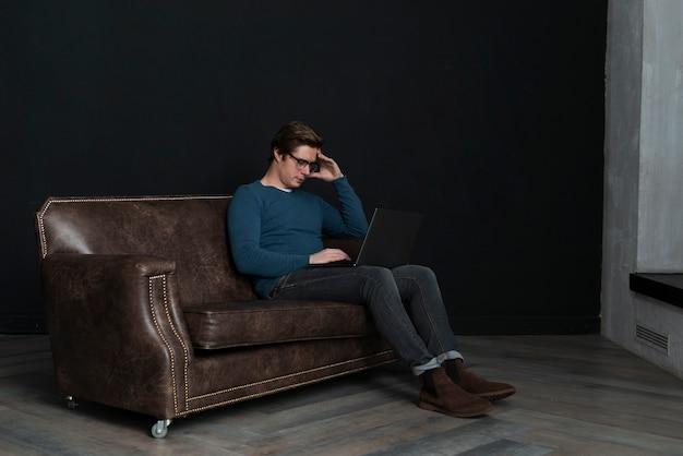 Homem de ângulo de visão remota olhando em seu laptop Foto gratuita