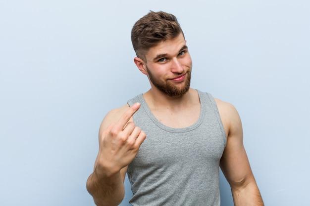 Homem de aptidão bonito jovem apontando com o dedo para você como se convidando chegar mais perto. Foto Premium
