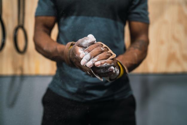 Homem de aptidão esfregando as mãos com pó de magnésio giz. Foto Premium