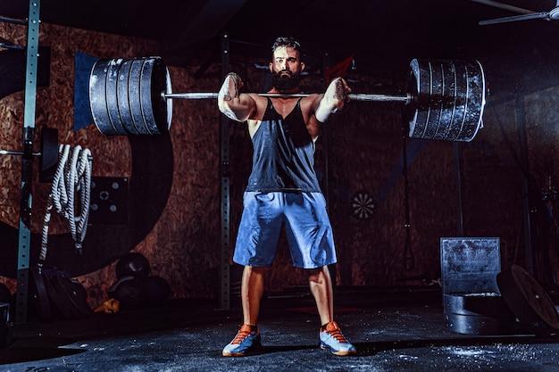 Homem de aptidão muscular fazendo levantamento terra um barbell na cabeça no moderno centro de fitness. treino funcional. Foto Premium