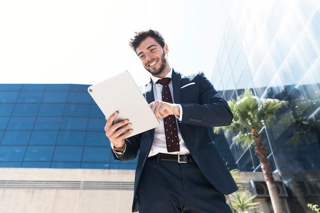 Homem de baixo ângulo sorridente com seu tablet Foto gratuita