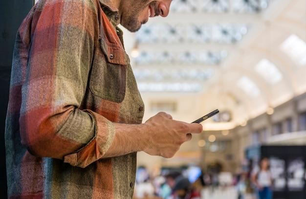 Homem de baixo ângulo usando smartphone Foto gratuita