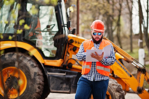 Homem de barba brutal trabalhador terno trabalhador da construção civil no capacete de segurança laranja, óculos de sol contra traktor com papel de plano nas mãos. Foto Premium