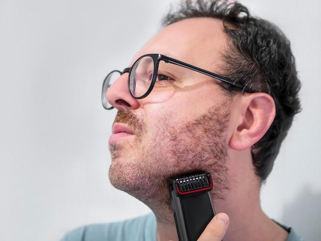 Homem de barba com aparador, barbeador elétrico Foto Premium