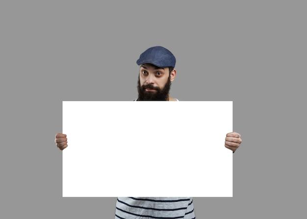 Homem de barba na camisa manter a folha em branco de papel branco para texto incert do produto ou vendas. Foto gratuita