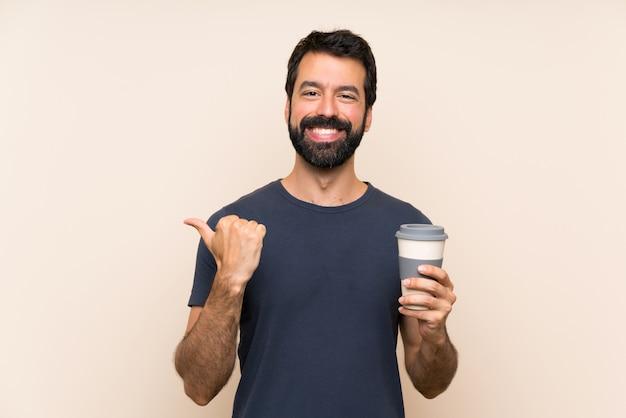 Homem de barba segurando um café apontando para o lado para apresentar um produto Foto Premium