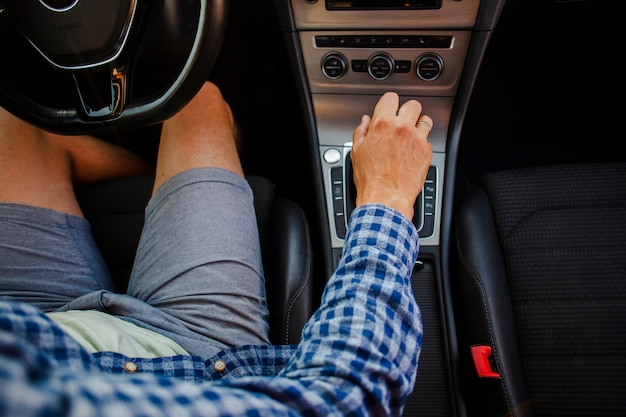 Homem de bermuda e camiseta, sentado no volante, segurando a caixa de velocidades Foto gratuita