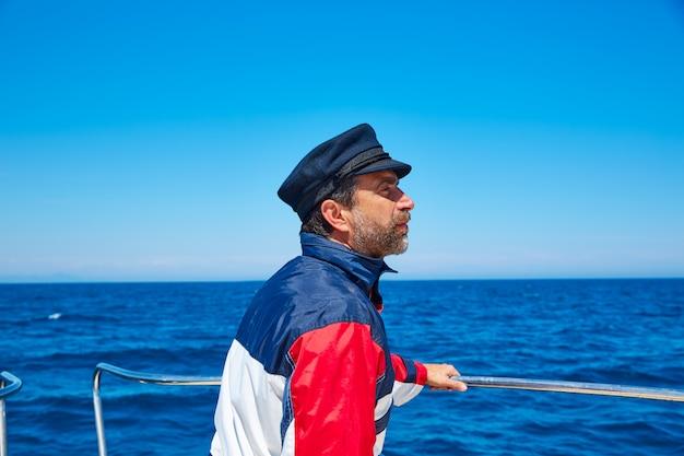 Homem de boné de marinheiro de barba navegando mar oceano em um barco Foto Premium
