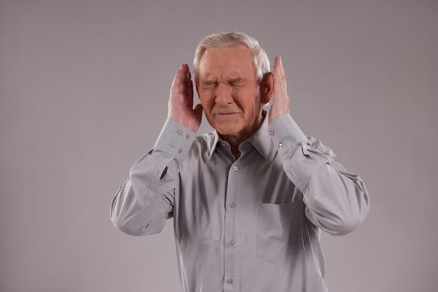Homem de cabelos grisalhos cobre as orelhas Foto Premium
