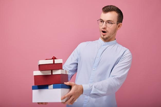 Homem de camisa azul céu mantém presentes em caixas nas mãos Foto Premium