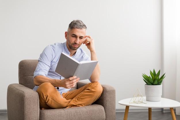 Homem de camisa azul lê um livro Foto gratuita