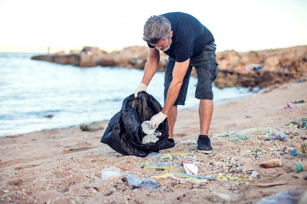 Homem de camisa escura e shorts com luvas brancas e um grande pacote preto coletando lixo na praia. proteção ambiental e conceito de poluição do planeta Foto Premium