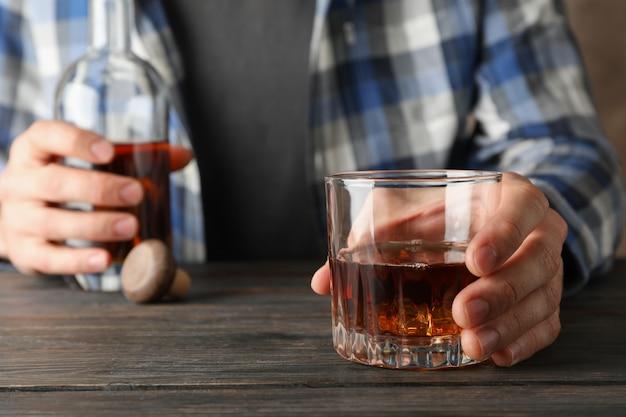 Homem de camisa mantém garrafa e copo de uísque na mesa de madeira, close-up Foto Premium