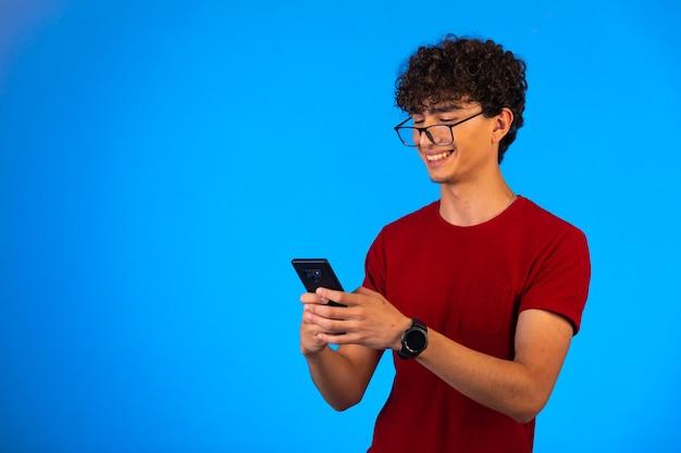 Homem de camisa vermelha tomando selfie em um smartphone em azul e rindo. Foto gratuita