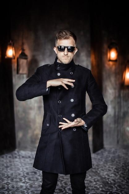 Homem de capa de chuva e óculos de sol está segurando as mãos como se houvesse algo entre eles Foto Premium