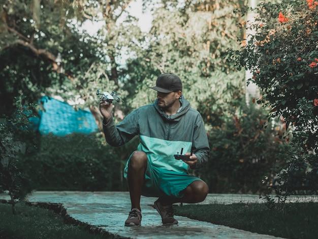 Homem de capuz colorido tem pequeno zangão compacto e controle remoto nas mãos. férias tropicais. imagem enfraquecida. Foto Premium