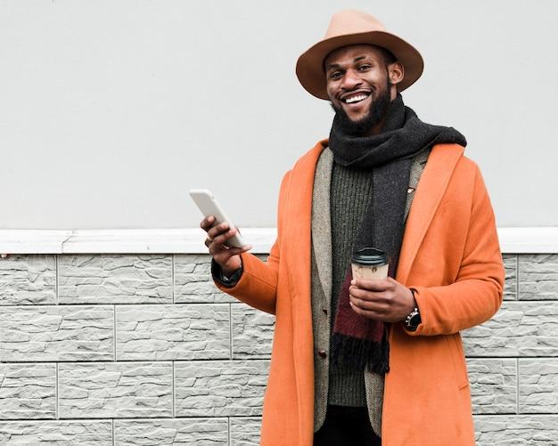 Homem de casaco laranja, segurando uma xícara de café e um telefone Foto gratuita