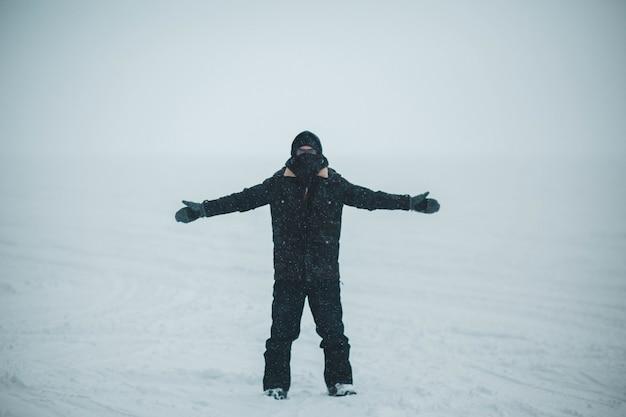 Homem de casaco preto e calça fica no chão coberto de neve Foto gratuita