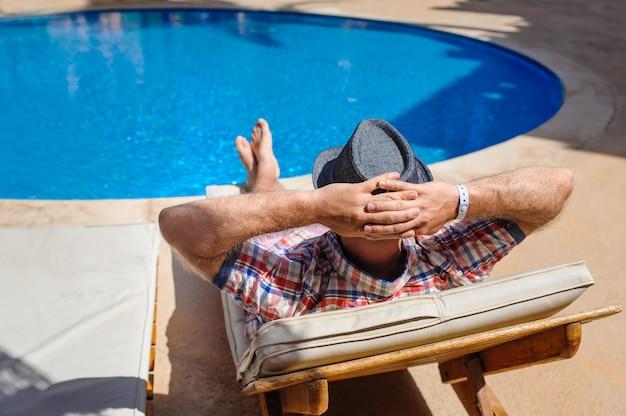 Homem de chapéu tomando sol em uma espreguiçadeira à beira da piscina Foto Premium